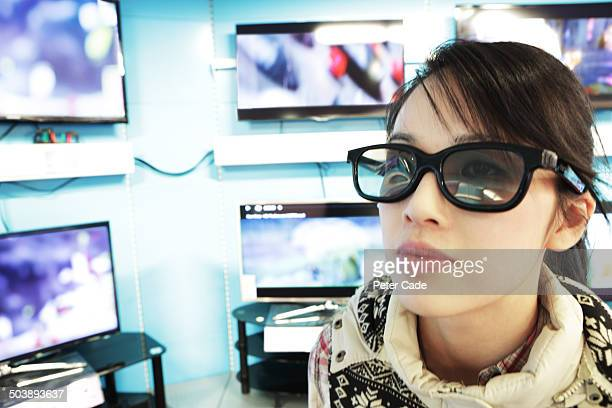 Woman wearing 3D glasses in television shop