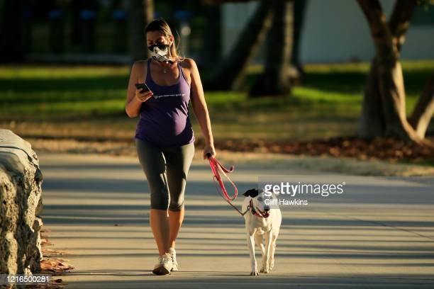 Woman wearing a bandana to cover her face walks her dog in Lummus Park on April 02, 2020 in Miami Beach, Florida. Florida Gov. Ron DeSantis signed a...