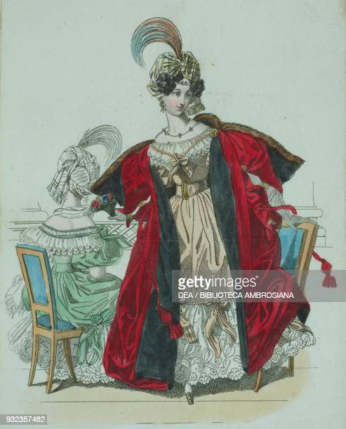 Woman wearing a beige dress with ample red velvet cloak fur shawl and hat with feathers and a woman wearing the same dress in green seated in the...