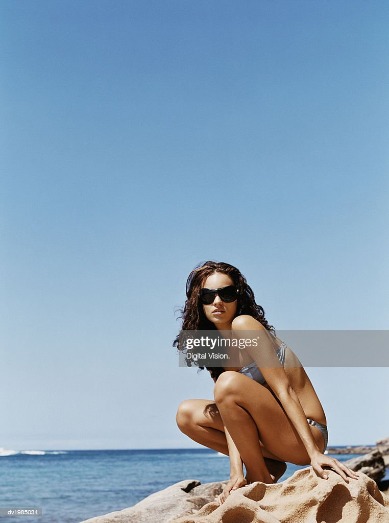 Woman Wearing a Bikini and Sunglasses Crouching on a Rock at the Water's Edge : Stock Photo