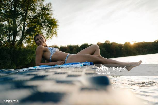 woman wearing a bikini lying on a float at a lake - pontoon bridge stock pictures, royalty-free photos & images