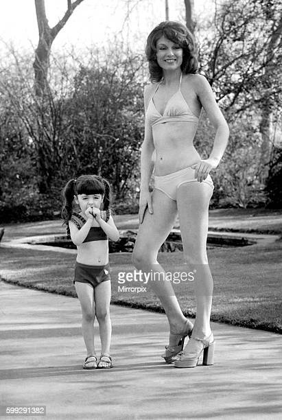 Woman wearing a bikini standing i n the park with a little girl February 1975 7501132