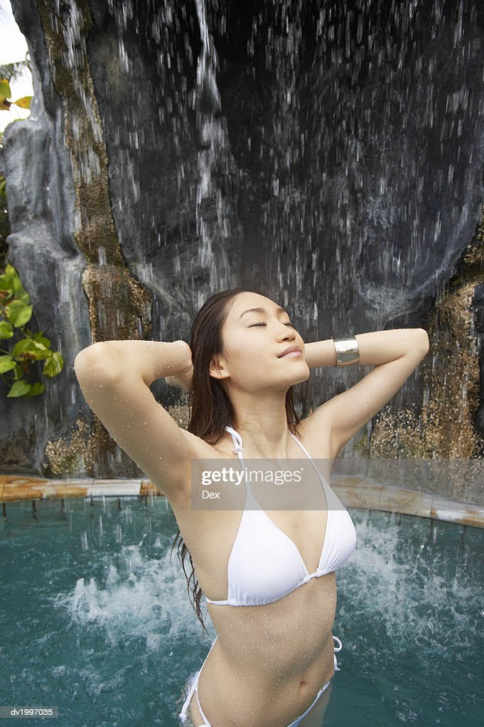 Woman Wearing a Bikini Standing Underneath a Waterfall : Stock Photo