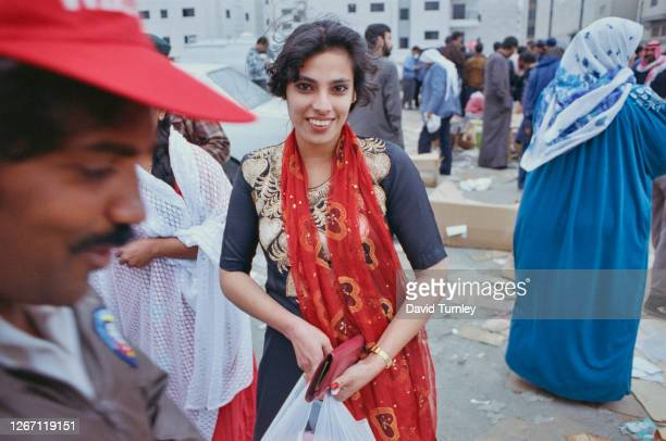 Woman wearing a black and gold dress with a diaphanous red scarf on a busy street after the liberation of Kuwait following the Iraqi retreat, Kuwait,...