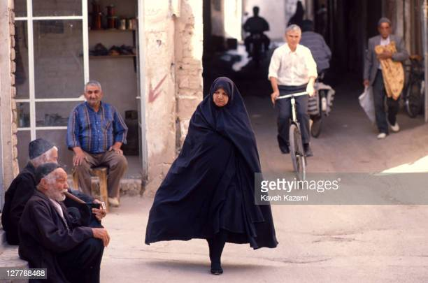 Woman wearing a black chador passes by an old man smoking a traditional pipe, at the bazaar in Kashan, Iran, 10th May 1994.