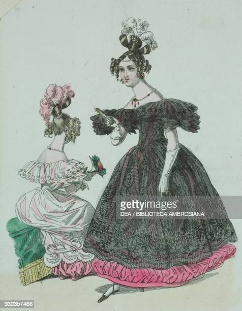 Woman wearing a black dress with embroidered decorations and white feathers in her hair woman wearing the same dress and light pink with matching bow...