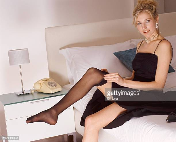 woman wearing a black evening dress sits on a bed putting on stockings - black dress with stockings foto e immagini stock