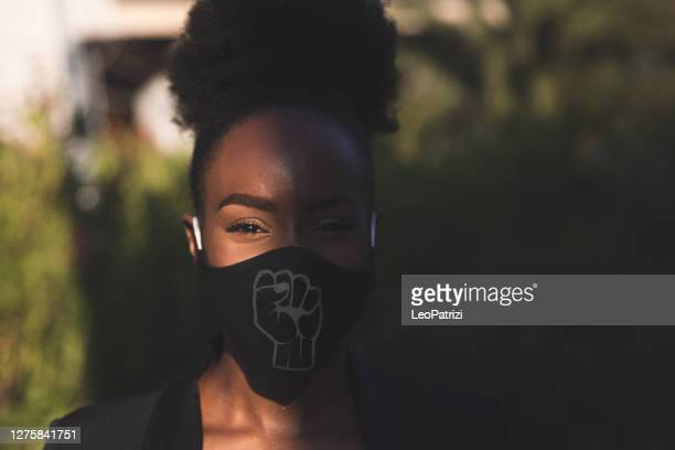 woman wearing a black face mask with a fist printed on it - anti racism stock pictures, royalty-free photos & images