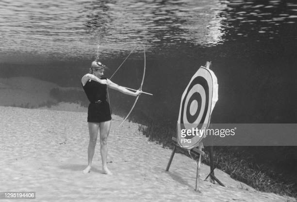 Woman wearing a black swimsuit stands with a bow and arrow, aiming for a target mounted on an easel underwater, location unknown, circa 1945.