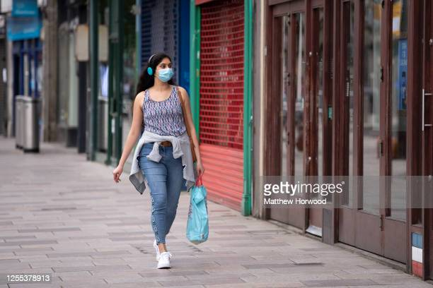 Woman wearing a blue surgical face mask walks passed a row of closed shops on July 09, 2020 in Cardiff, United Kingdom.Many UK businesses are...
