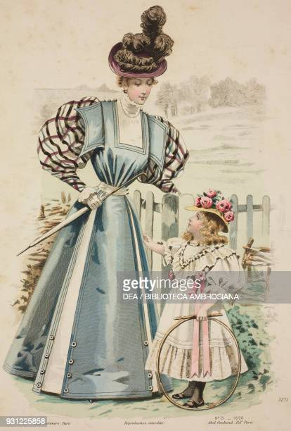 Woman wearing a blue walking dress with checkedpuffed sleeves and carrying an umbrella girl wearing a pink and white walking dress and hat with...
