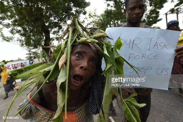 TOPSHOT A woman wearing a branch of leaves on her head reacts as she and other evictees of OtodoGbame a Lagos shanty town march to press for relief...