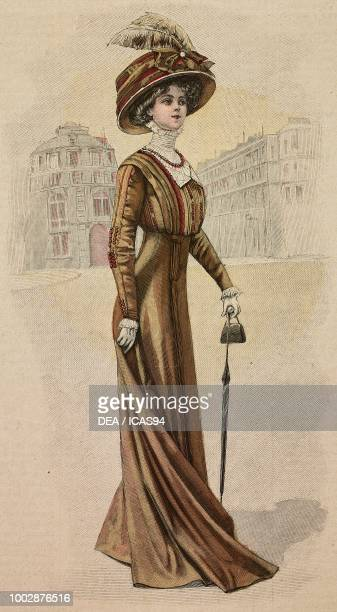 Woman wearing a brown Drap walking dress brown muslin and tulle corset and a hat with feathers creation by Alice Blum colored engraving from La Mode...