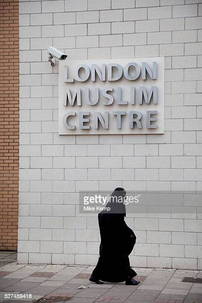 Woman wearing a burkha passes the London Muslim Centre under a CCTV surveillance camera on Whitechapel High Street in East London. This area in the...