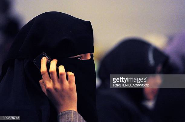 A woman wearing a burqa talks on a mobile phone during the 'Uprising in the Muslim World' Khilafah Conference 2011 in Sydney on July 3 2011 Around...