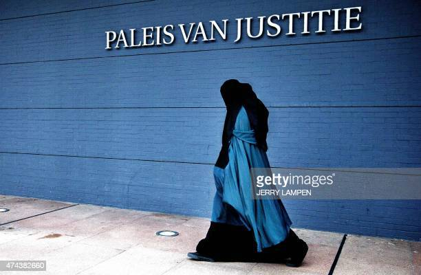 A woman wearing a burqa walks past the Palace of Justice in The Hague on December 1 2014 The Dutch cabinet approved on May 22 2015 a partial ban on...