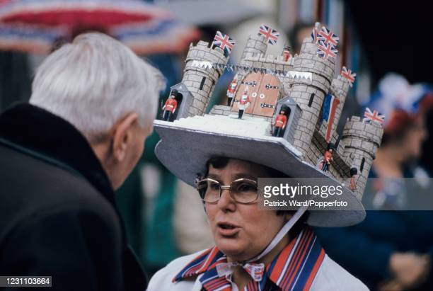 Woman wearing a cardboard hat designed as a castle including guards and flags whilst celebrating the Silver Jubilee of Queen Elizabeth II at a street...