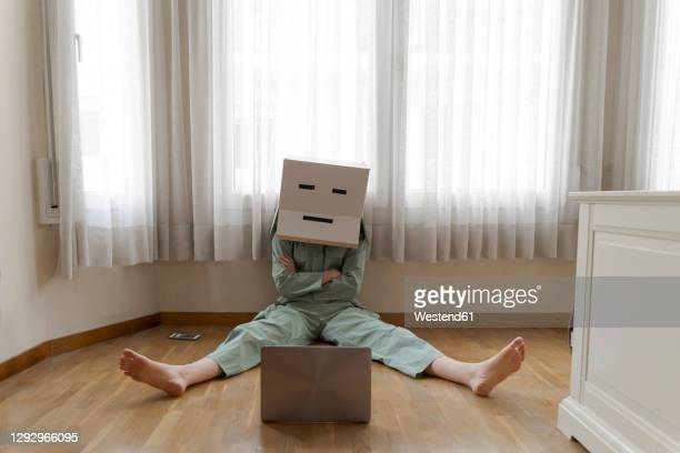 woman wearing a cardbox on head with bored smiley sitting on floor and looking at laptop - crisis stock pictures, royalty-free photos & images