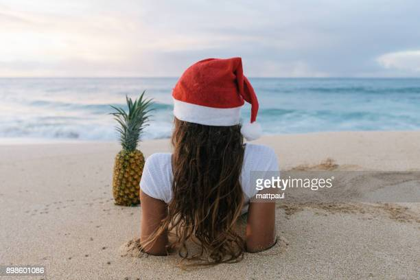 woman wearing a christmas santa hat lying on beach next to a pineapple, haleiwa, hawaii, america, usa - beach christmas stock pictures, royalty-free photos & images