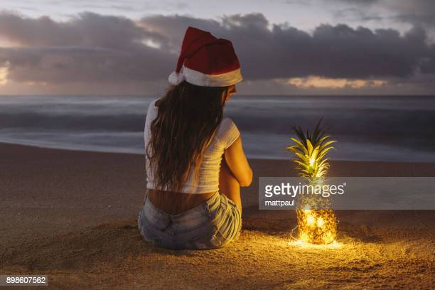 woman wearing a christmas santa hat sitting on beach next to an illuminated pineapple, haleiwa, hawaii, america, usa - hawaii christmas stock pictures, royalty-free photos & images