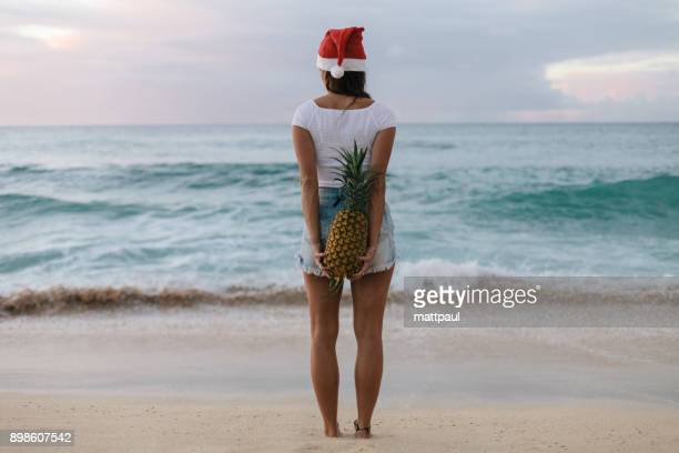 woman wearing a christmas santa hat standing on the holding a pineapple behind her back, haleiwa, hawaii, america, usa - hawaii christmas stock pictures, royalty-free photos & images