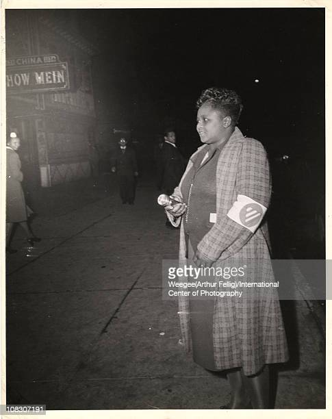 A woman wearing a civilian defense air raid warden arm band and holding a flashlight stands on the sidewalk at night New York 1945 Photo by...