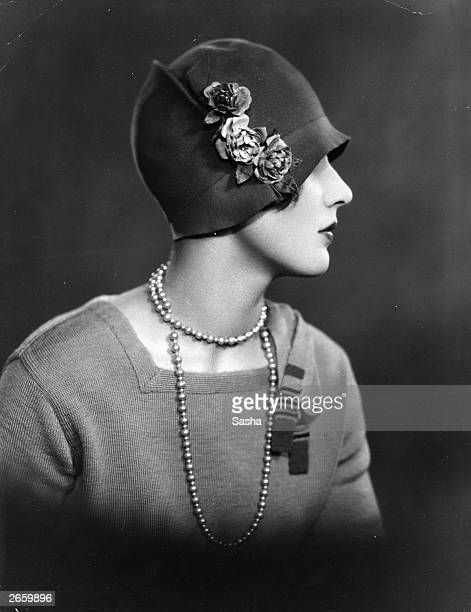 A woman wearing a cloche hat decorated with flowers