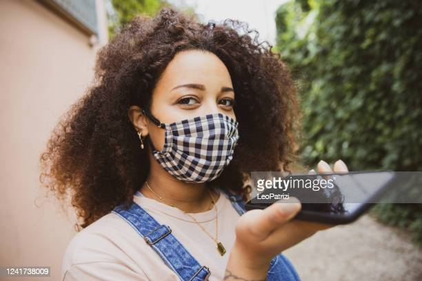 woman wearing a cloth face mask sending a vocal message - speech recognition stock pictures, royalty-free photos & images