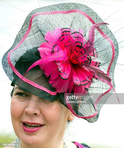 A woman wearing a colourful fascinator looks on from the Grandstand ahead of the horse racing on Derby day at the Epsom Derby Festival in Surrey...