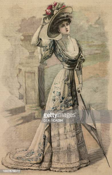 Woman wearing a cream Crepe de Chine afternoon dress with embroidery and Valenciennes lace inserts draped corset and a hat with flowers creation by...