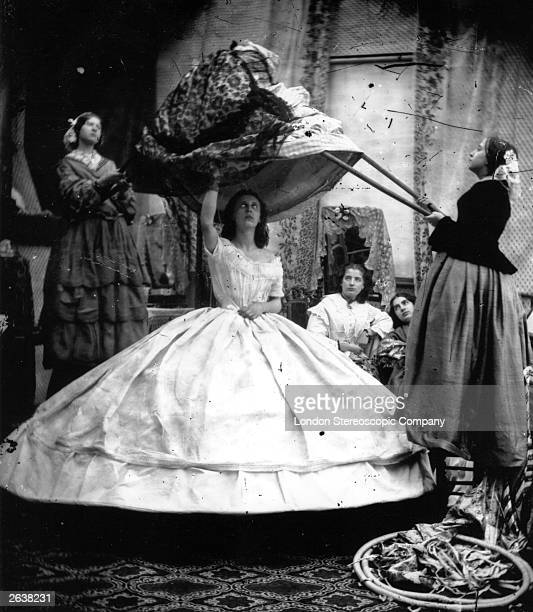 A woman wearing a crinoline being dressed with the aid of long poles to lift her dress over the hoops