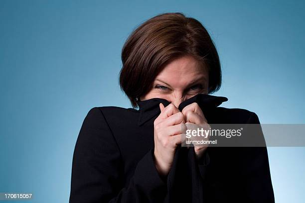 A woman wearing a dark dress trying to hide her face