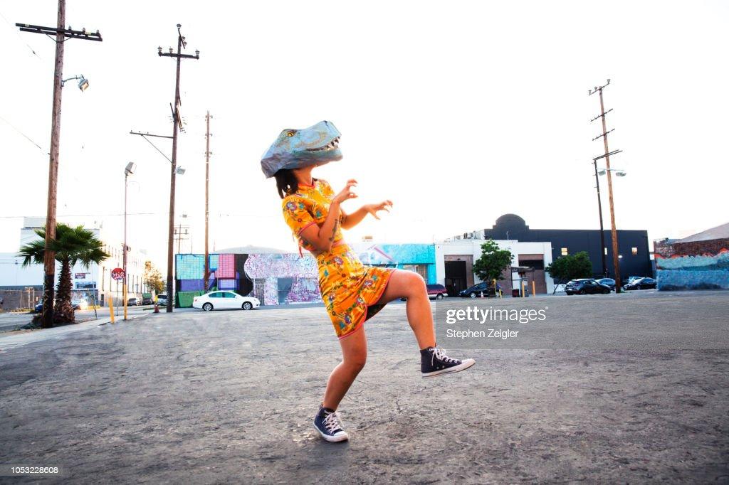 Woman wearing a dinosaur mask : Stockfoto