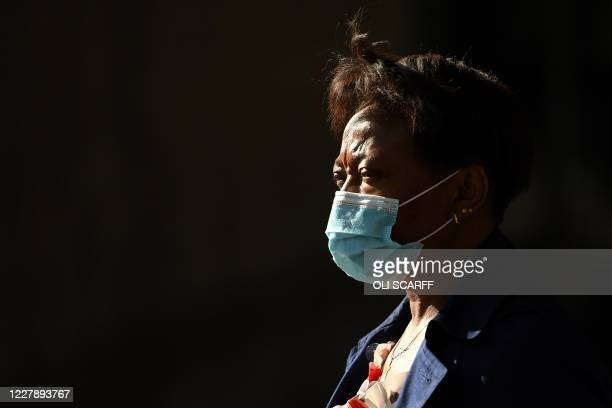 Woman wearing a disposable face mask or covering due to the COVID-19 pandemic, walks in the evening sun in Manchester, northwest England on August 3...