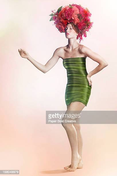 Woman wearing a dress and hat made of plants