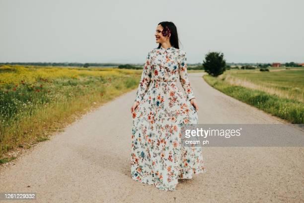 femme utilisant une robe marchant sur une journée ensoleillée dans la nature - robe à motif floral photos et images de collection
