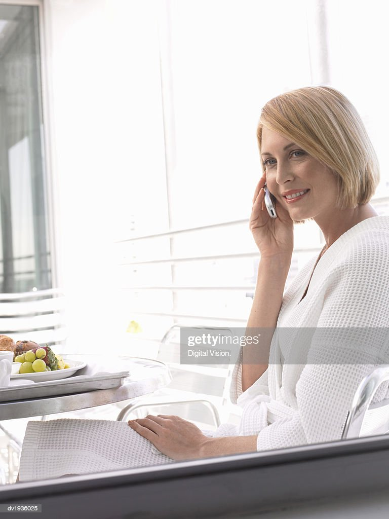 Woman Wearing a Dressing Gown and Using a Mobile Phone : Stock Photo