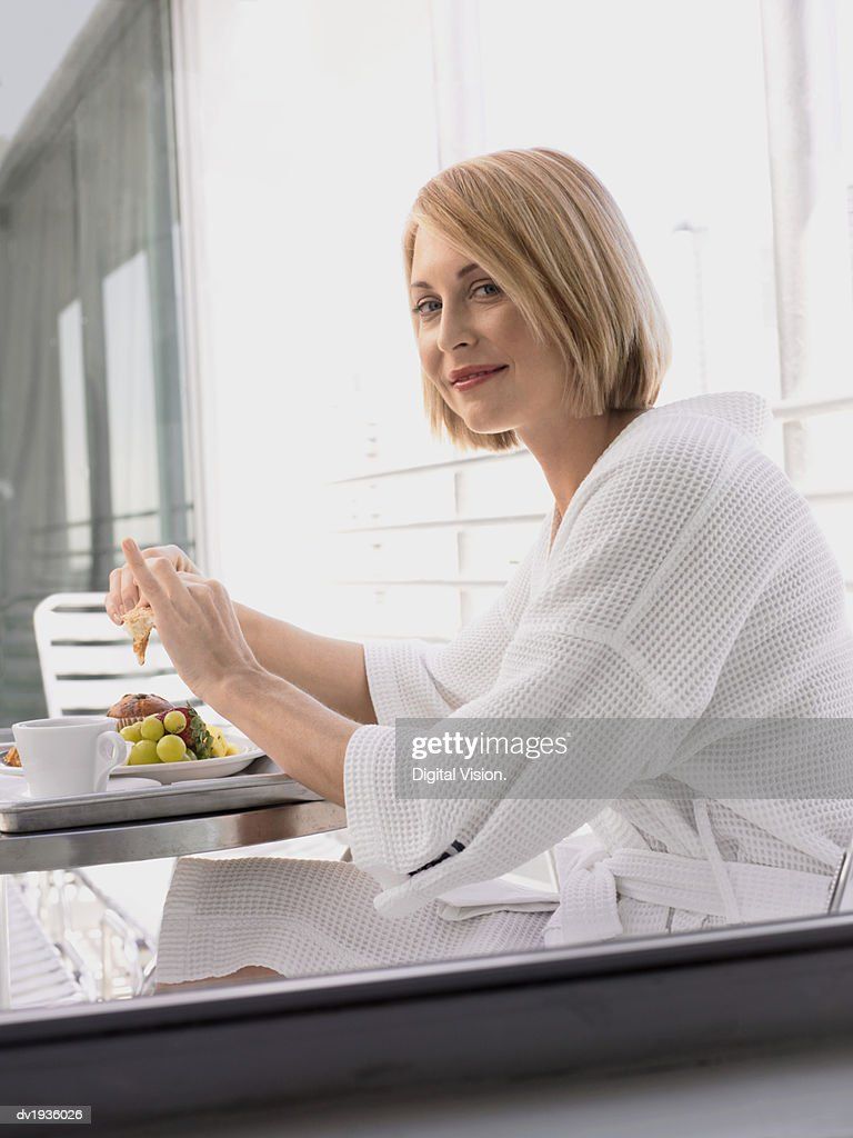 Woman Wearing a Dressing Gown, Sitting at a Metallic Table and Having Breakfast in a Hotel : Stock Photo