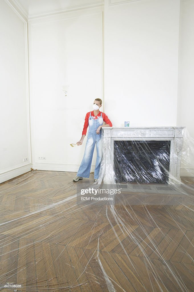 Woman Wearing a Dust Mask and Holding a Paintbrush in an Empty Living Room Covered with Plastic Sheeting : Stock Photo