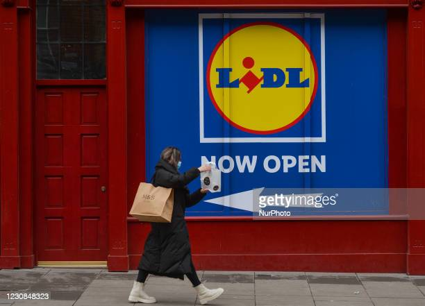 Woman wearing a face cover walks by LIDL shop in Dublin city centre during Level 5 Covid-19 lockdown. In Dublin during Level 5 Covid-19 lockdown. On...