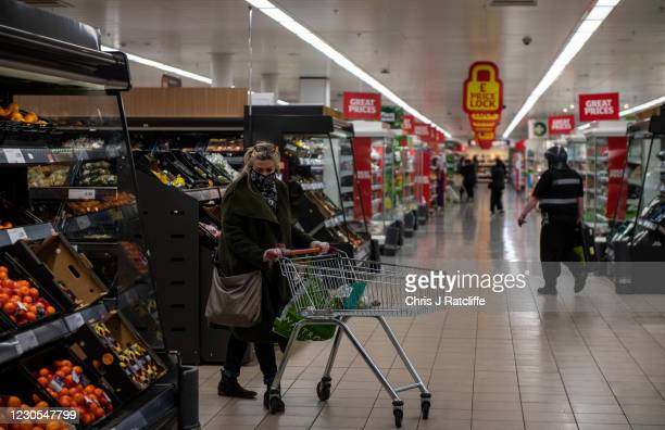 Woman wearing a face covering and gloves shops in a Sainsburys supermarket on January 12, 2021 in Tunbridge Wells, United Kingdom. In response to...