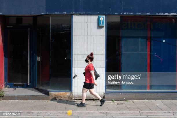 Woman wearing a face covering walks passed a closed William Hill store on August 12, 2020 in Cardiff, Wales. The Office For National Statistics...