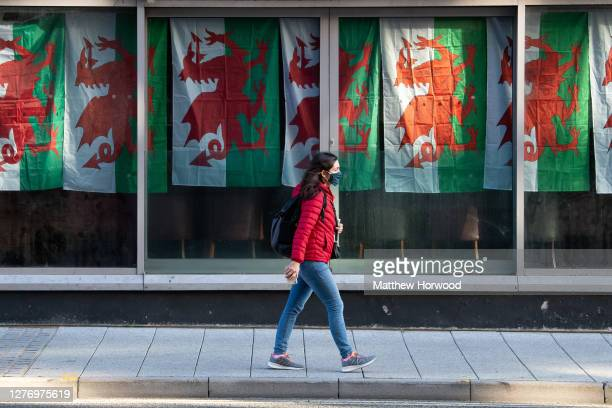 Woman wearing a face covering walks past a nightclub with Wales flags hanging in their window on September 27, 2020 in Cardiff, Wales. A local...