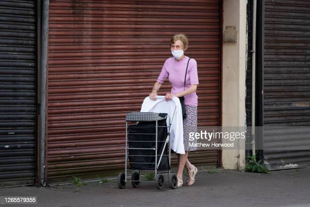 Woman wearing a face face mask walks past closed stores on Cowbridge Road East on August 12, 2020 in Cardiff, Wales. The Office For National...