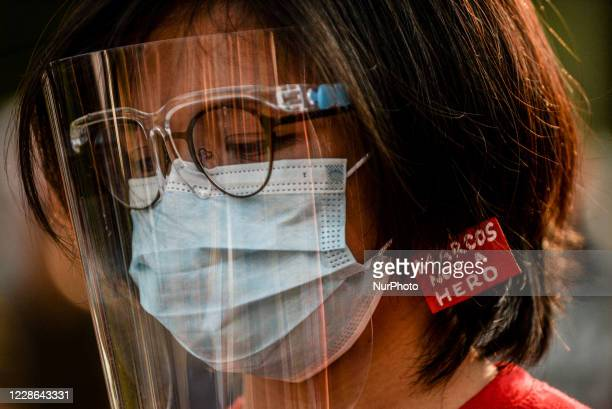 """Woman wearing a face mask, a face shield, and an earring with the text """"Marcos Not A Hero"""" joins a protest during the 48th anniversary of..."""