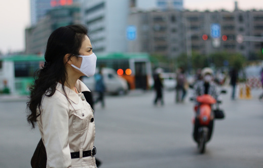Woman wearing a face mask against pollution or disease 147268329