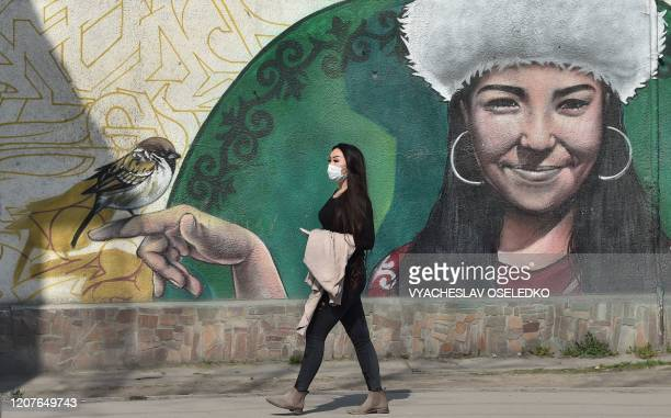 Woman wearing a face mask, amid concerns of the COVID-19 coronavirus, walks past a graffiti in Bishkek on March 19, 2020.