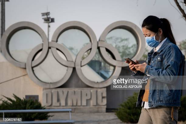 Woman wearing a face mask, amid concerns of the COVID-19 coronavirus, walks before an Olympic rings sculpture at the national 'Birds Nest' stadium,...