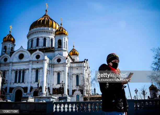 Woman wearing a face mask, amid concerns over the spread of the COVID-19 coronavirus, walks past the Cathedral of Christ the Saviour in downtown...