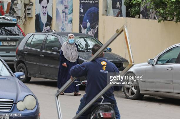 A woman wearing a face mask amid coronavirus fears crosses a street with a portrait of Iran's former Supreme Leader Ayatollah Ruhollah Khomeini...